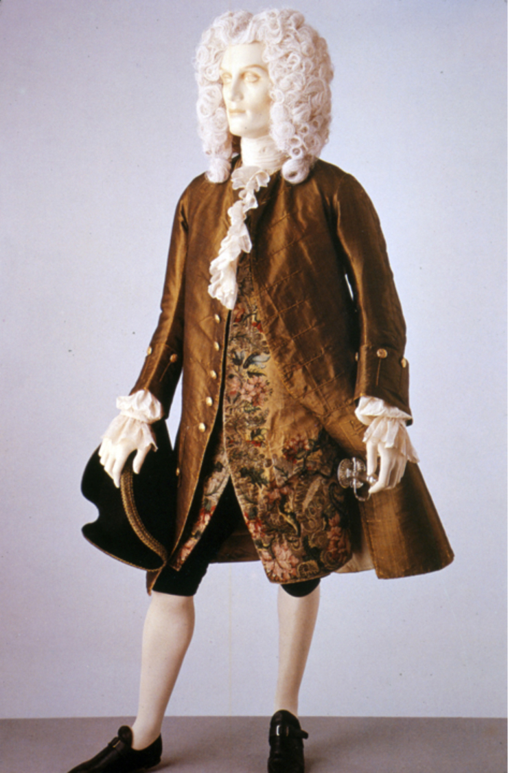 """This coat and waistcoat illustrate formal daywear for men in the 1740s. The fabric of the coat is a rich shot green and black silk. By the 1740s the waistcoat is shorter in length than the coat. It is made of yellow silk brocaded with coloured silk and silver threads. Comprised of large flowers and leaves densely covering the fabric, the brocaded pattern is typical of Late Baroque design. The coat is collarless. It fits tightly to the body, but has very full skirts pleated to the sides at the hip. The sleeve cuffs are wide, reaching about half way to the elbow. Typical of the early 18th century, the waistcoat is also sleeved, although this style was beginning to go out of fashion by the 1740s."" Victoria & Albert Museum, 1745"